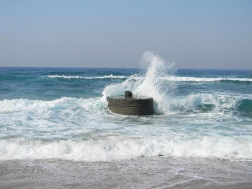 Hibberdene concrete pillar in the waves breaking on the beach